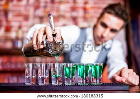 Bartender pouring blue curacao alcoholic cocktail in glasses on bar - stock photo