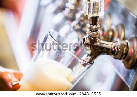 Bartender pouring draft beer in the bar. - stock photo