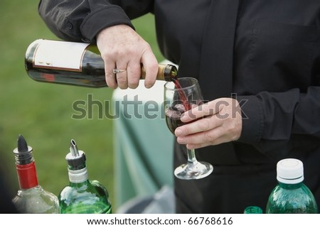 Bartender pouring glass of red wine from bottle - stock photo