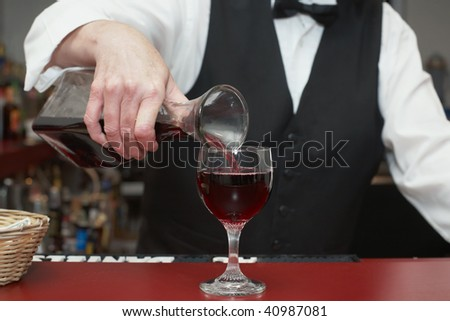 Bartender pouring glass of red wine from decanter - stock photo