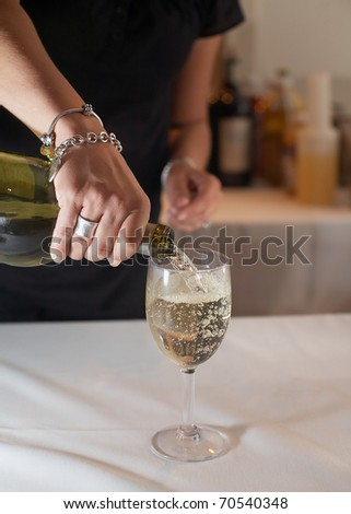 Bartender pouring glass of white wine from bottle - stock photo