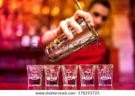 Bartender pouring strong alcoholic drink into shots at nightclub - stock photo