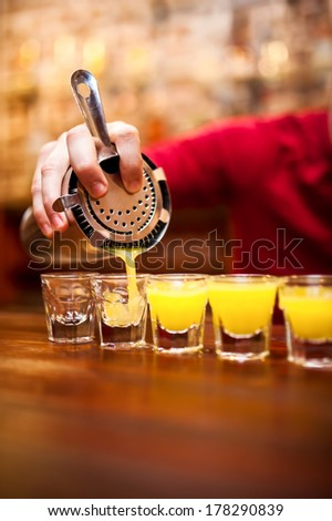 Bartender pouring strong alcoholic drink into small glasses on bar - stock photo