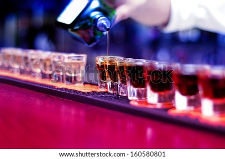 Bartender pouring strong alcoholic drink into small glasses on bar, shots - stock photo