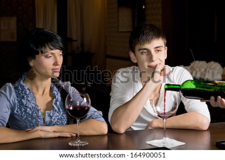 Bartender pouring wine watched by a young couple seated at the counter as he refills the mans glass from a bottle - stock photo
