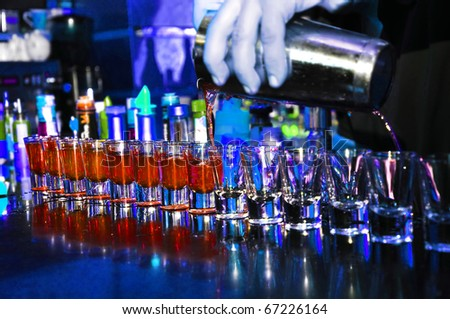 Bartender pours alcoholic drink into small glasses for customers - stock photo