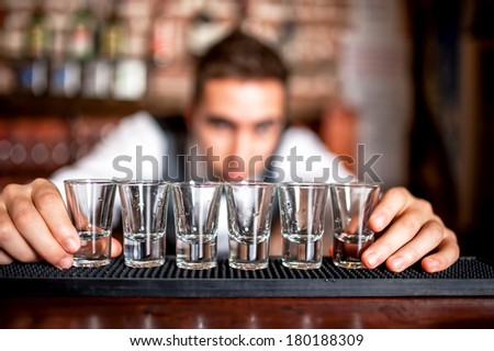 bartender preparing and lining shot glasses for alcoholic drinks on bar - stock photo