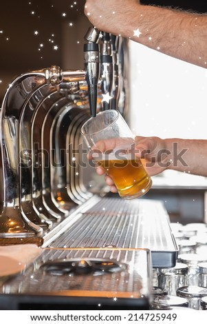 Bartender pulling a pint of beer against night sky