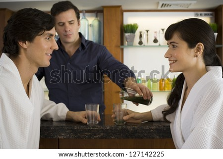 Bartender serving a young couple at a bar counter - stock photo