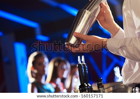 Bartender shaking a cocktail, young women on the background - stock photo
