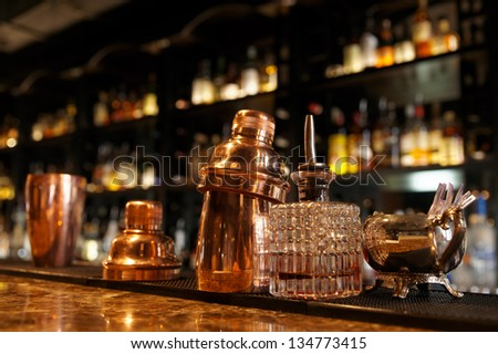 Bartender tools sitting on bar counter - stock photo