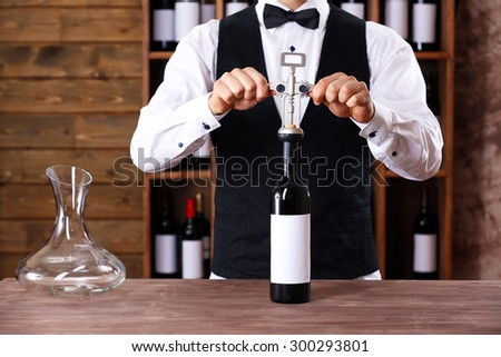 Bartender working at counter on bar background - stock photo