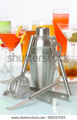 Bartending tools with a variety of drinks and cocktails in background - stock photo