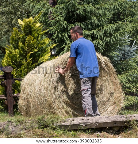 BARTNE, POLAND - JULY 11, 2015: Farmer working at his farmland at the end of summer. Regietow, Poland