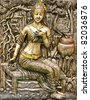 bas-relief decorated on temple's wall showing Thai's ancient woman sitting in front of a tree - stock photo