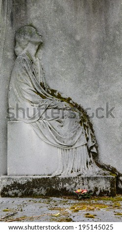 Bas-relief depicting a mourning young woman on headstone at  Montparnasse Cemetery in Paris (France)  - stock photo