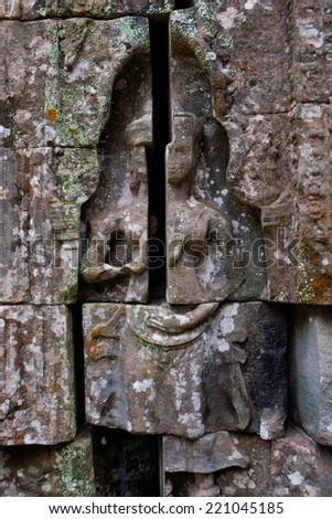 Bas-relief depicting ancient stories on the walls of  Ta Phrom temple ruins, Angkor Wat Cambodia. - stock photo
