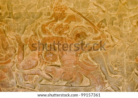 Bas relief showing a scene from the Battle of Lanka between Rama and Ravana as described in the epic Ramayana.  A monkey soldier is fighting a demon.  Wall of Angkor Wat Temple, Angkor, Cambodia.