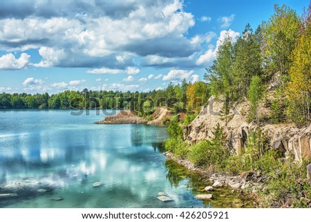 Basalt lake in the woods on the site of an old quarry. - stock photo
