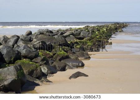 Basalt stone mole from beach into the sea. - stock photo