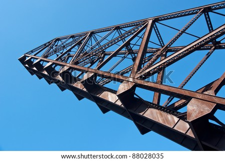 Bascule Bridge Arm:  The swing arm of an abandoned railroad bascule drawbridge is permanently in a fully raised position so ship traffic on the Cuyahoga River in Cleveland, Ohio can pass below it. - stock photo