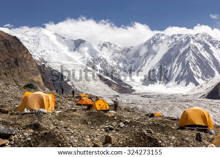 Base Camp of High Altitude Expedition Many Orange Tents Located on Side Rock Moraine of Glacier in Severe Snow and Ice Peaks Valley - stock photo