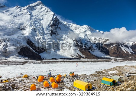 Base Camp of High Altitude Mountain Expedition Many Orange Tents Located on Side Rock Moraine of Glacier in Severe Snow and Ice Peaks Landscape - stock photo