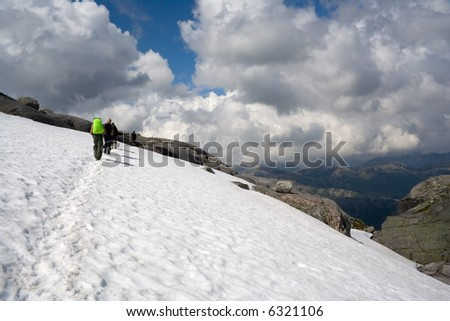 BASE-jumpers hiking by the trail through the snow field. Kjerag mountains, Norway. - stock photo