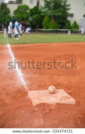 baseball and base on baseball field with players on background - stock photo