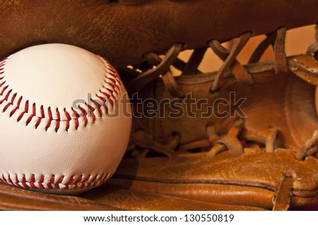 baseball and baseball glove on red background