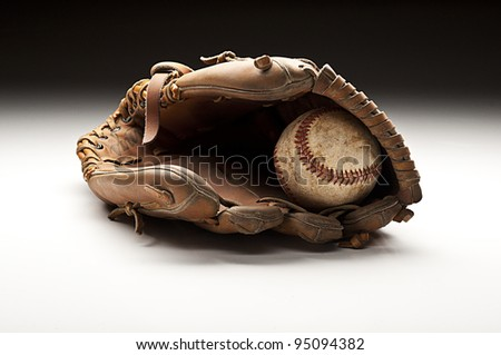 Baseball and glove on a table top. - stock photo