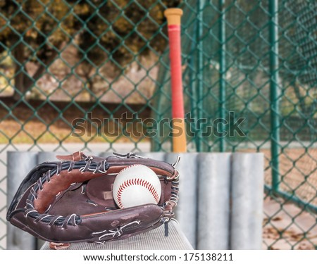 Baseball and glove resting on metal bench in dugout. Ball inside mitt. Low angle view. Baseball bat and storage rack, chain link fence in blurred background. Horizontal view. - stock photo