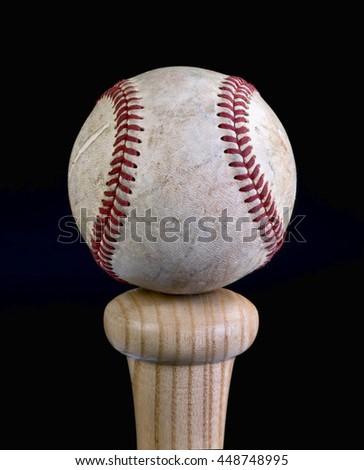Baseball balanced on  handle of wooden bat .. - stock photo
