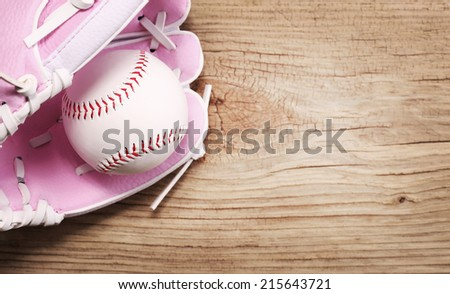 Baseball. Ball in Pink Female Glove over wood background with copy space.  - stock photo