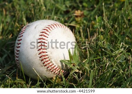 Baseball ball on green grass - stock photo