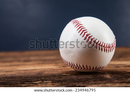 Baseball ball on wooden table and blue backgdound - stock photo