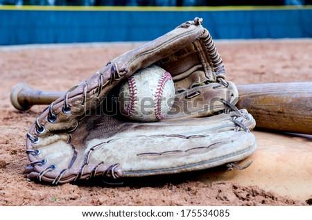 Baseball bat, glove, and ball on base on field.   - stock photo
