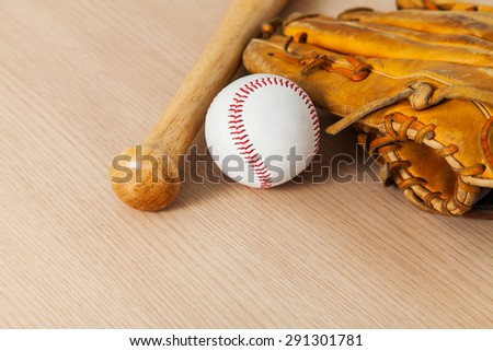 Baseball bat with ball and baseball glove on wood background - stock photo