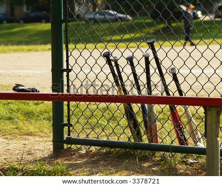 baseball bats leaning against a baseball backstop - stock photo