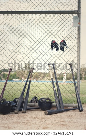 Baseball bats leaning against dugout fence. Processed with retro feel - stock photo