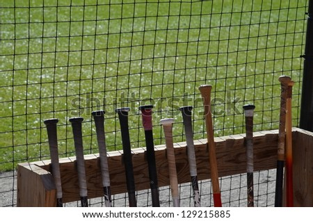 Baseball bats lines up in the dugout. Ready for the game. - stock photo