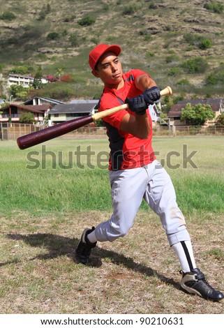 Baseball batter mid-swing in an open grassy field - stock photo