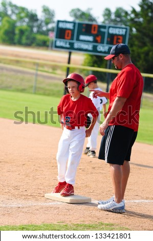 Baseball coach giving instruction to player at first base during a game. - stock photo