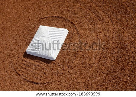 Baseball diamond base surrounded with groomed dirt at a school softball field - stock photo