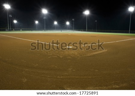Baseball diamond, view from home plate, under the night time lights - stock photo