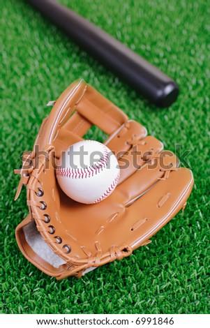 Baseball equipment against green grass - stock photo