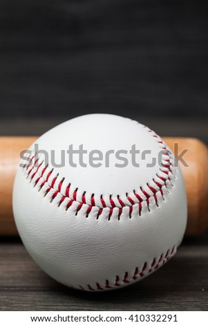 Baseball equipment: wooden bat and ball on a wood plank or bench background