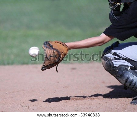 Baseball flying into a waiting catcher's mitt. Focus on mitt; ball slightly blurred to show speed and motion. - stock photo