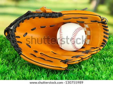 Baseball glove and ball on grass in park - stock photo