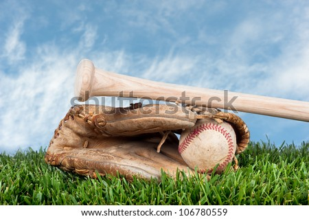 Baseball glove, ball, and bat laying on grass against a blue, lightly cloudy sky for placement of copy. - stock photo